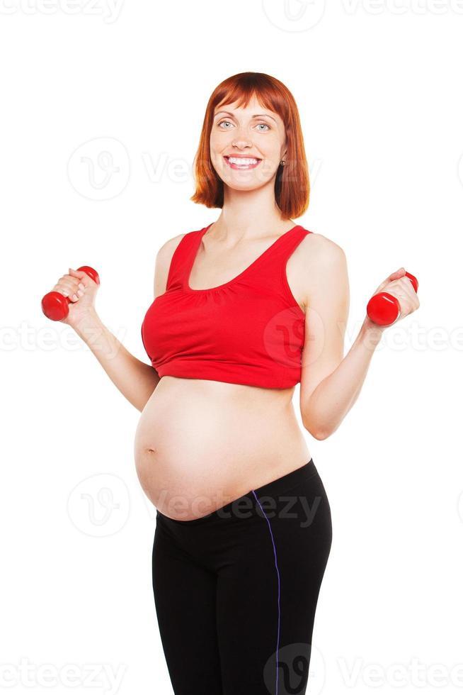 schöne schwangere Frau, die Übung mit Hanteln tut. Gesundheitswesen. isoliert über foto