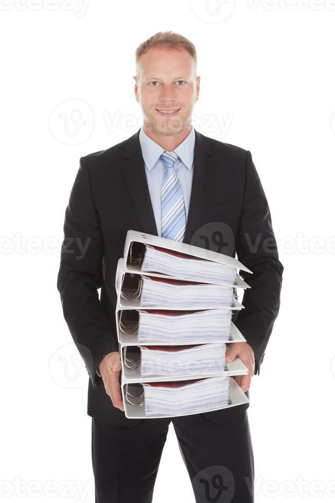 Geschäftsmann, der Stapel von Bindemitteln trägt foto