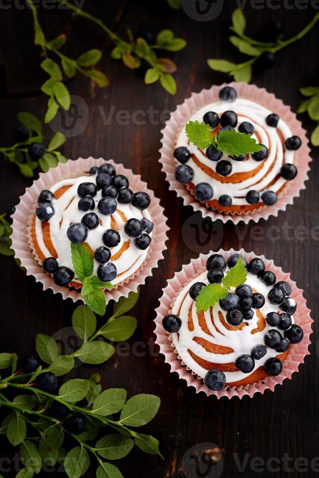 hausgemachte Cupcakes mit Zuckerguss und Blaubeeren foto