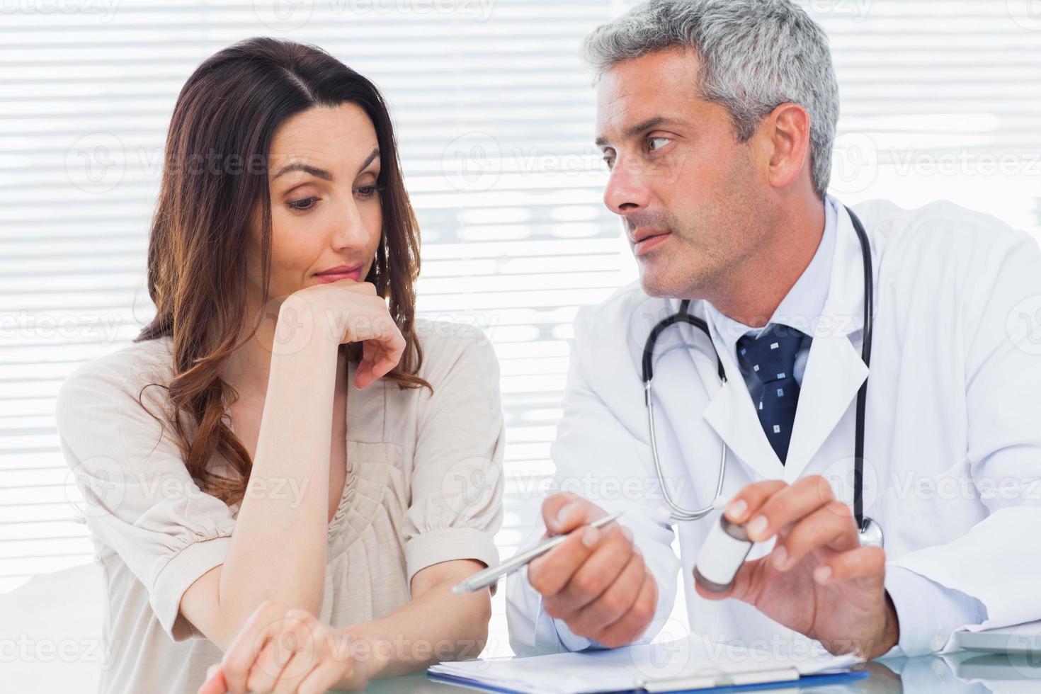 ernsthafter Arzt, der seinem Patienten zuhört foto