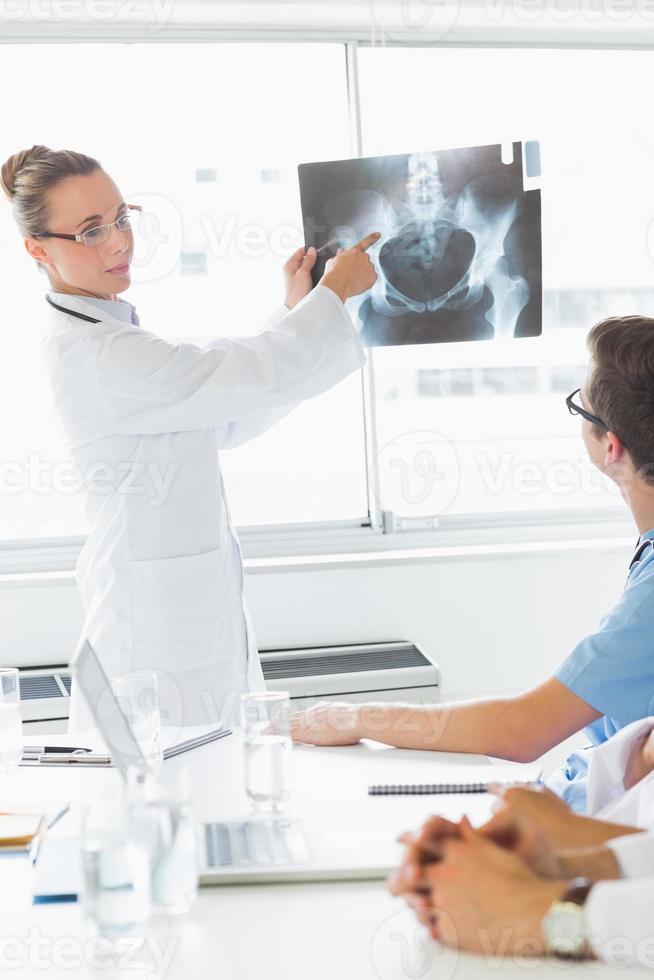 professioneller Arzt, der Kollegen Röntgenstrahlen zeigt foto