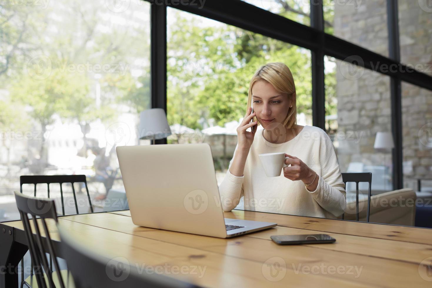 weiblicher Hipster, der Smartphone-Gespräch am Holztisch arbeitet foto