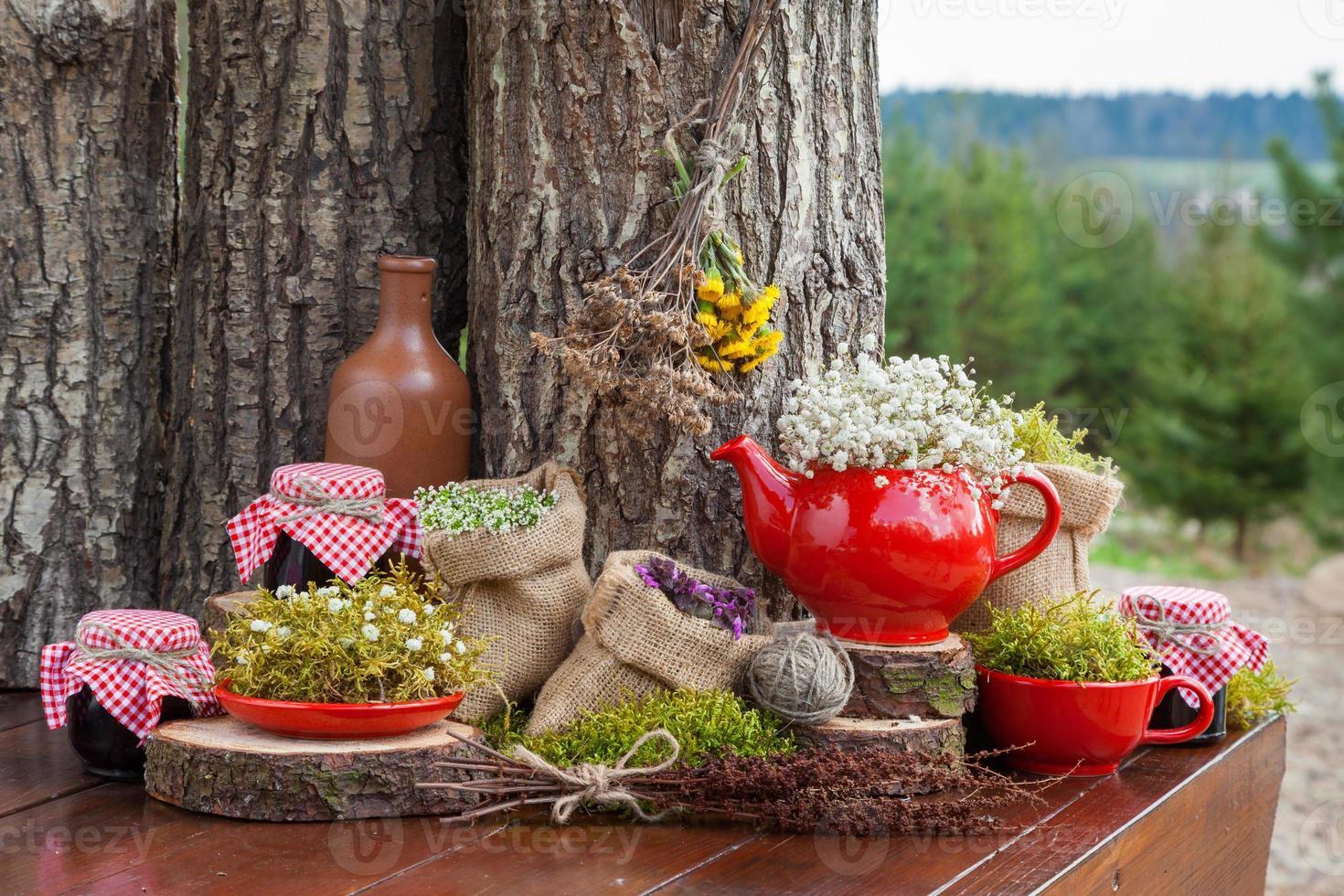 Beutel mit Heilkräutern, roter Teekanne und Marmeladengläsern foto