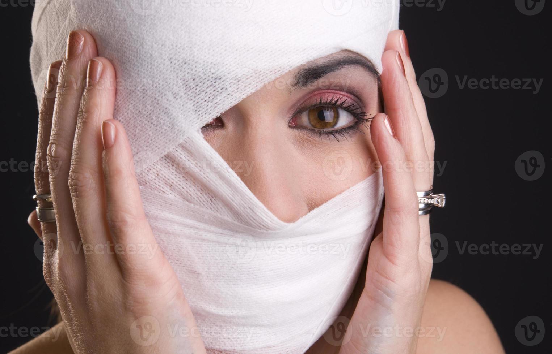Frau extreme Schmerzen Hände halten Kopf gewickelt Erste Hilfe foto