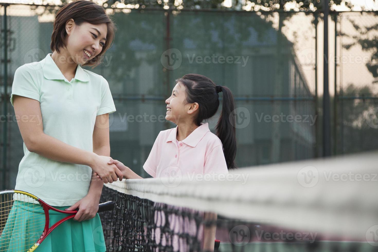 Mutter und Tochter Händeschütteln über das Tennisnetz foto