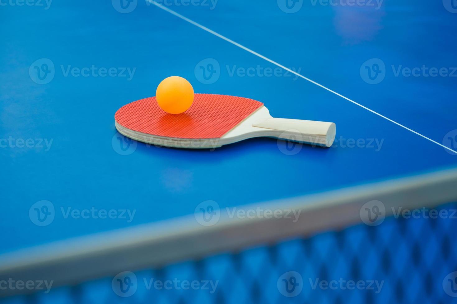 Tischtennisschläger und Ball & Netz auf Tischtennisplatte vertikal foto