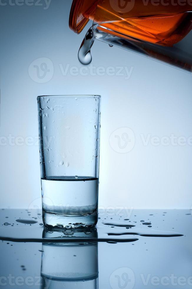 Wasser wird aus dem Filter in ein Glas gegossen foto