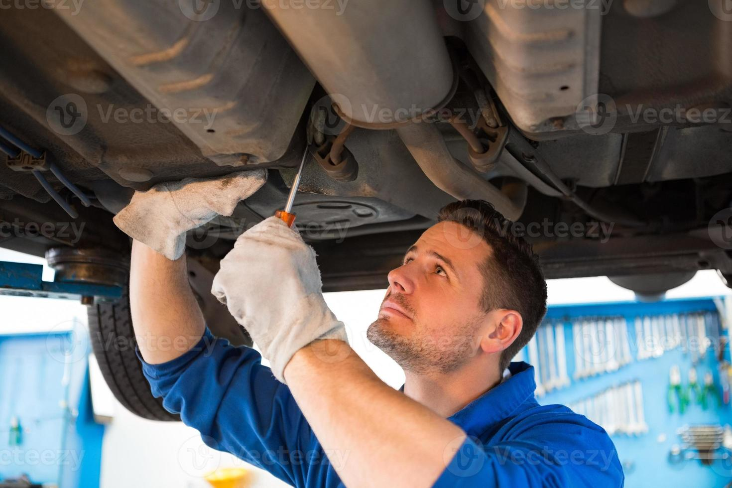 Mechaniker untersucht unter dem Auto foto
