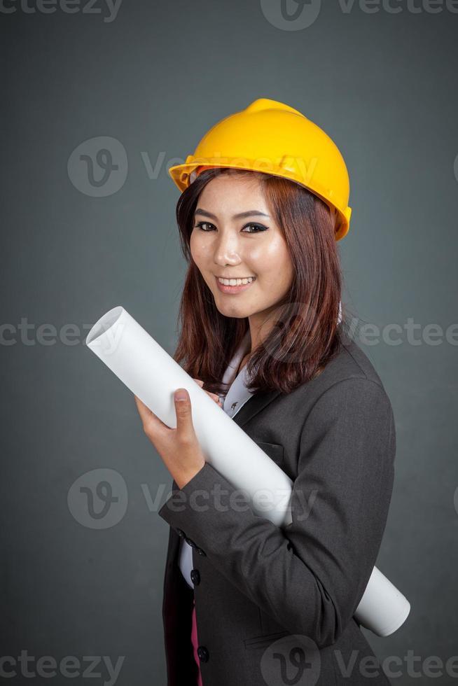 asiatische Ingenieurin Mädchen halten eine Blaupause und lächeln foto