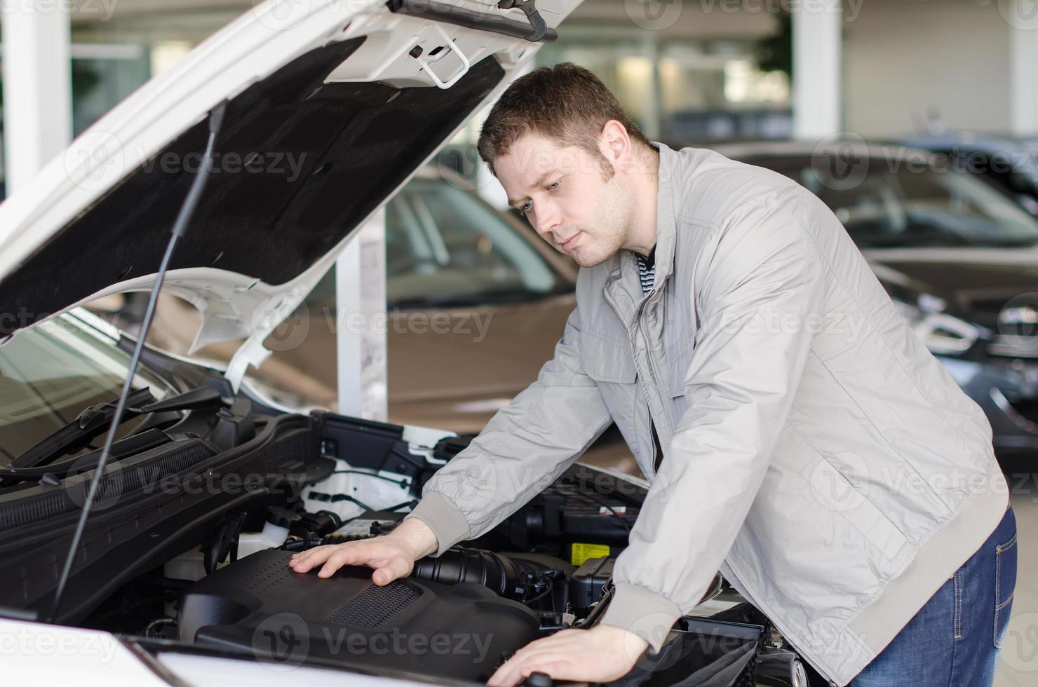 Mann untersucht neues Auto im Autohaus. foto