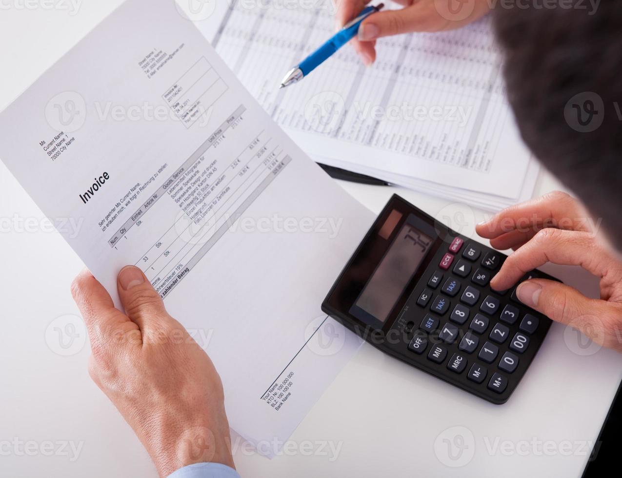 Mann prüft eine Rechnung auf einem Taschenrechner foto