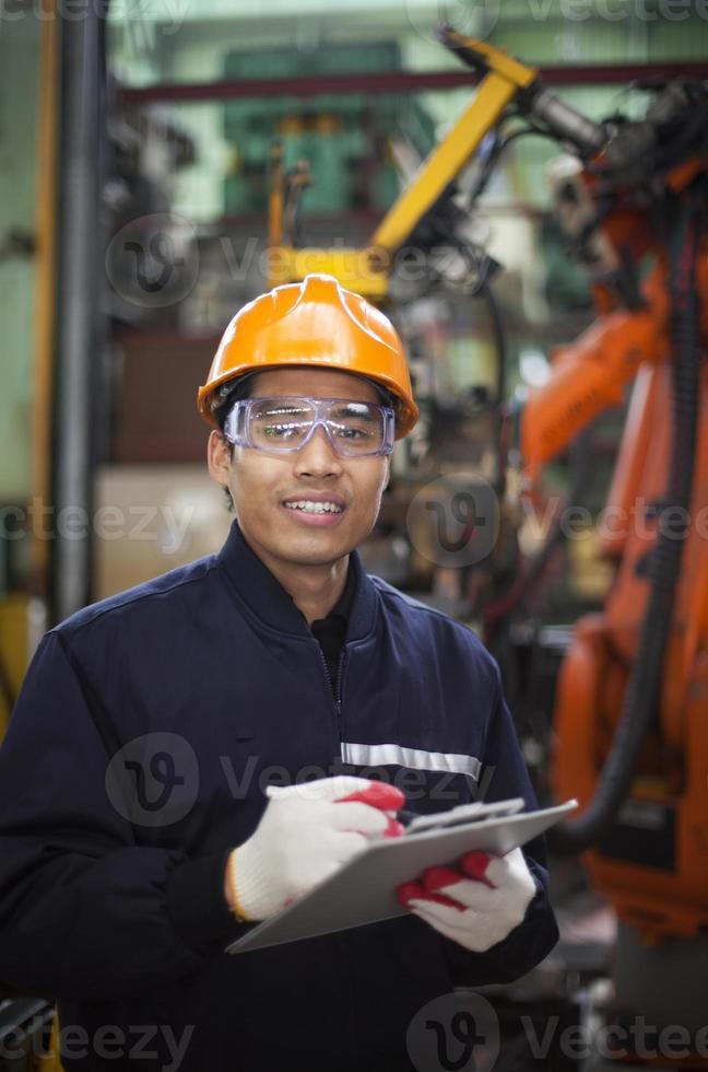 junger Mann im Schutzhelm, der auf Zwischenablage in der Fabrik schreibt foto