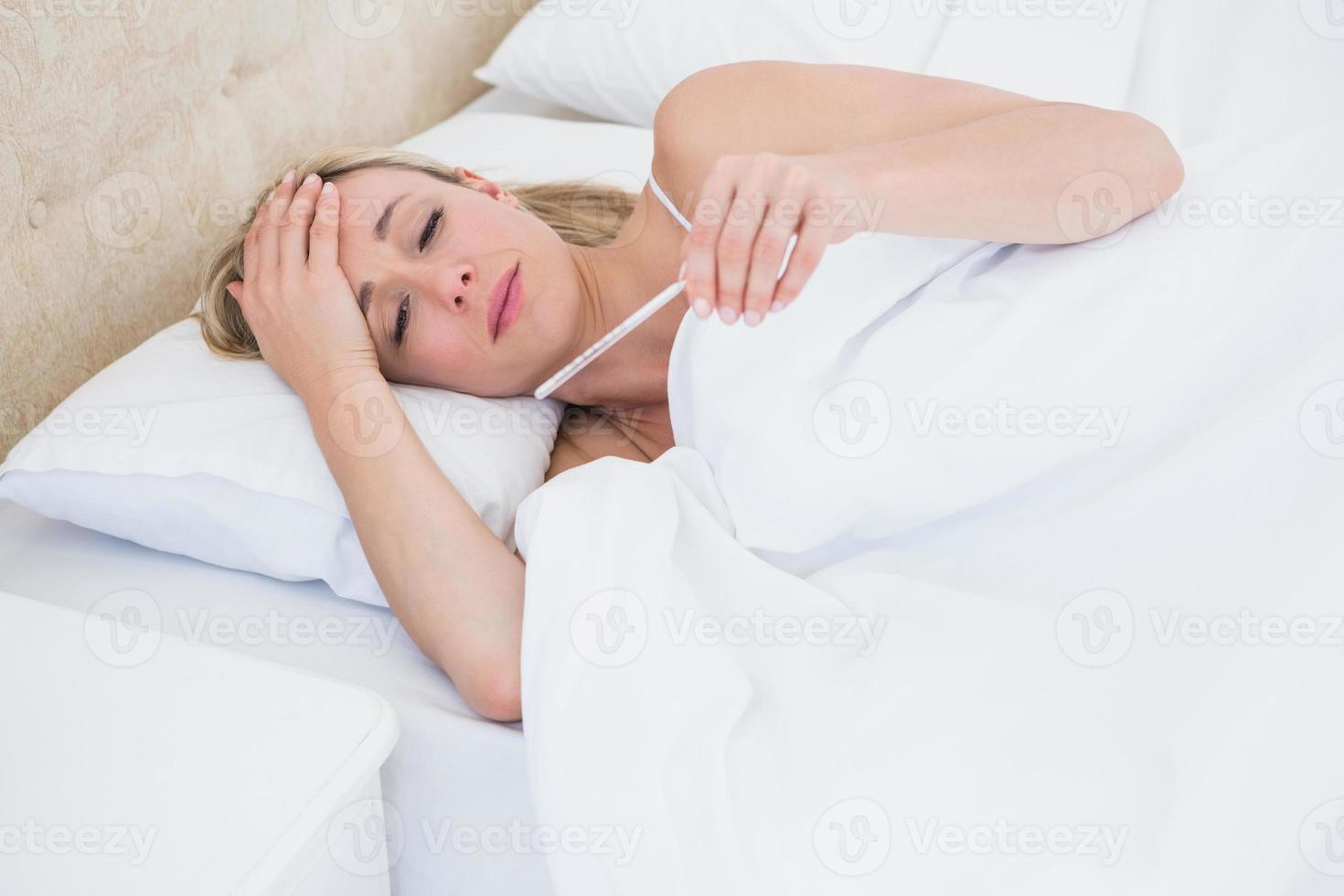 blonde Frau überprüft ihre Temperatur foto