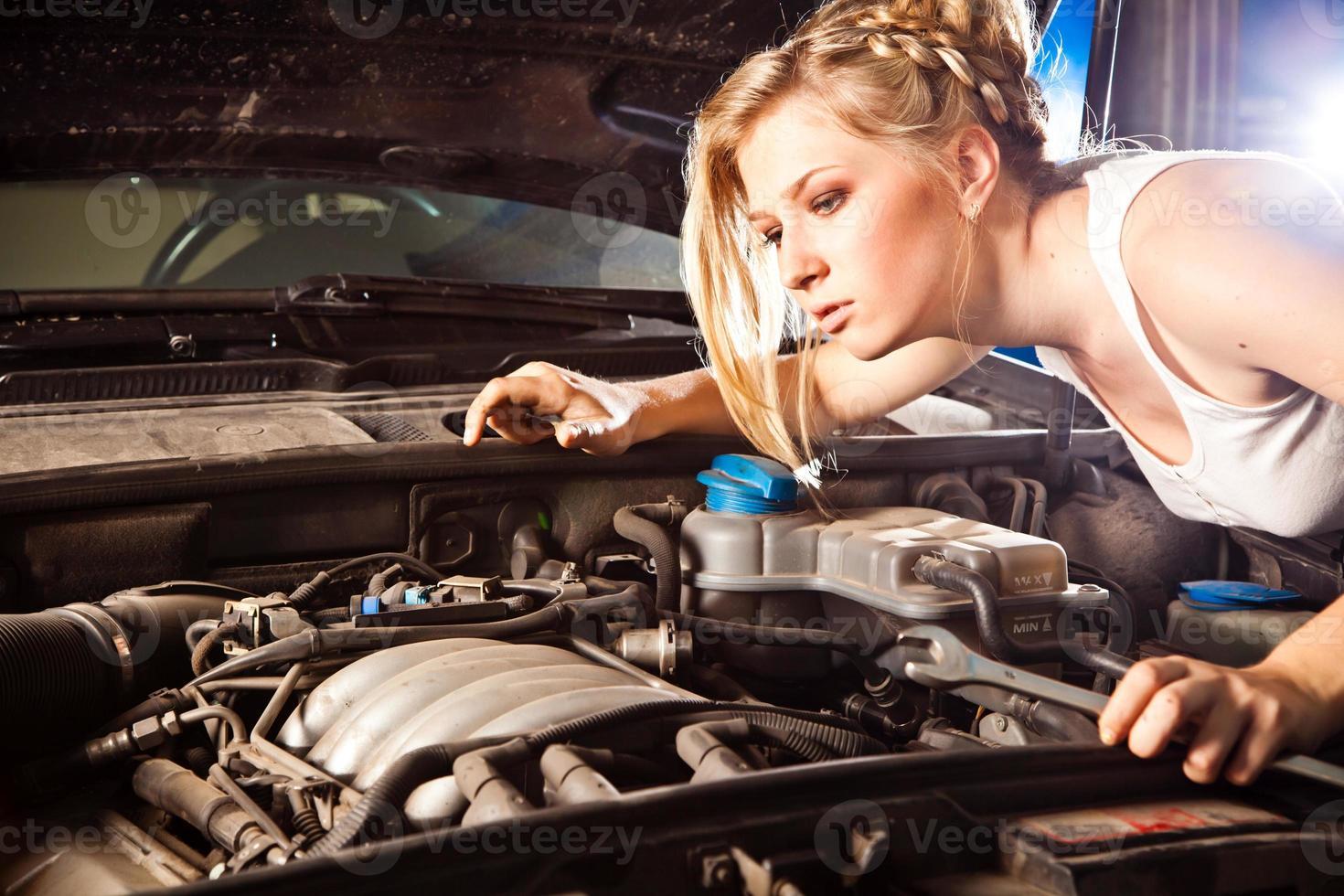 Mädchen versucht, kaputtes Auto zu reparieren foto