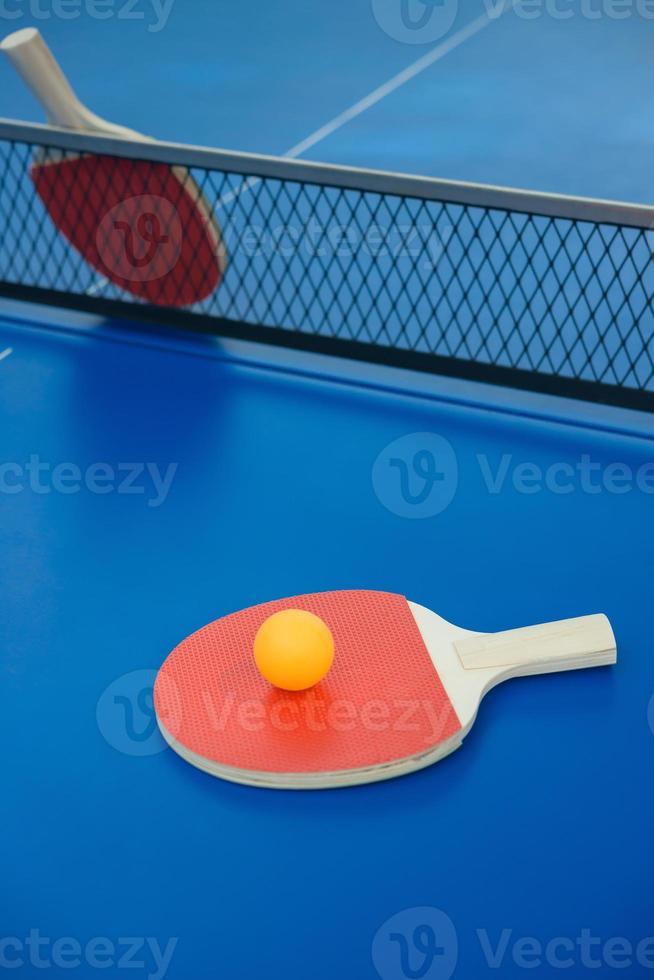 Pingpongschläger und Ball auf einer blauen Tischtennisplatte foto