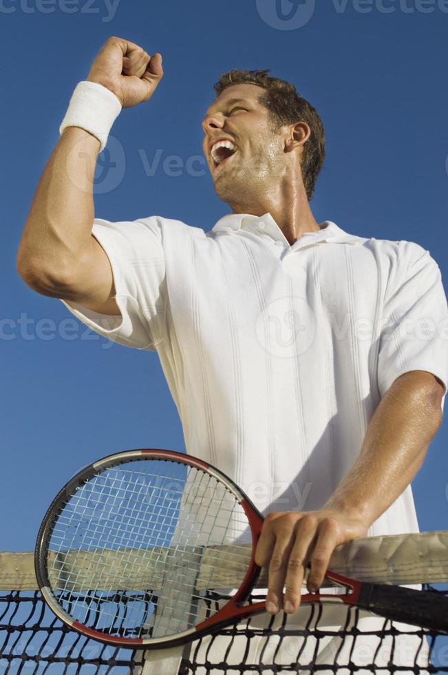 Tennisspieler pumpt mit der Faust ins Netz foto