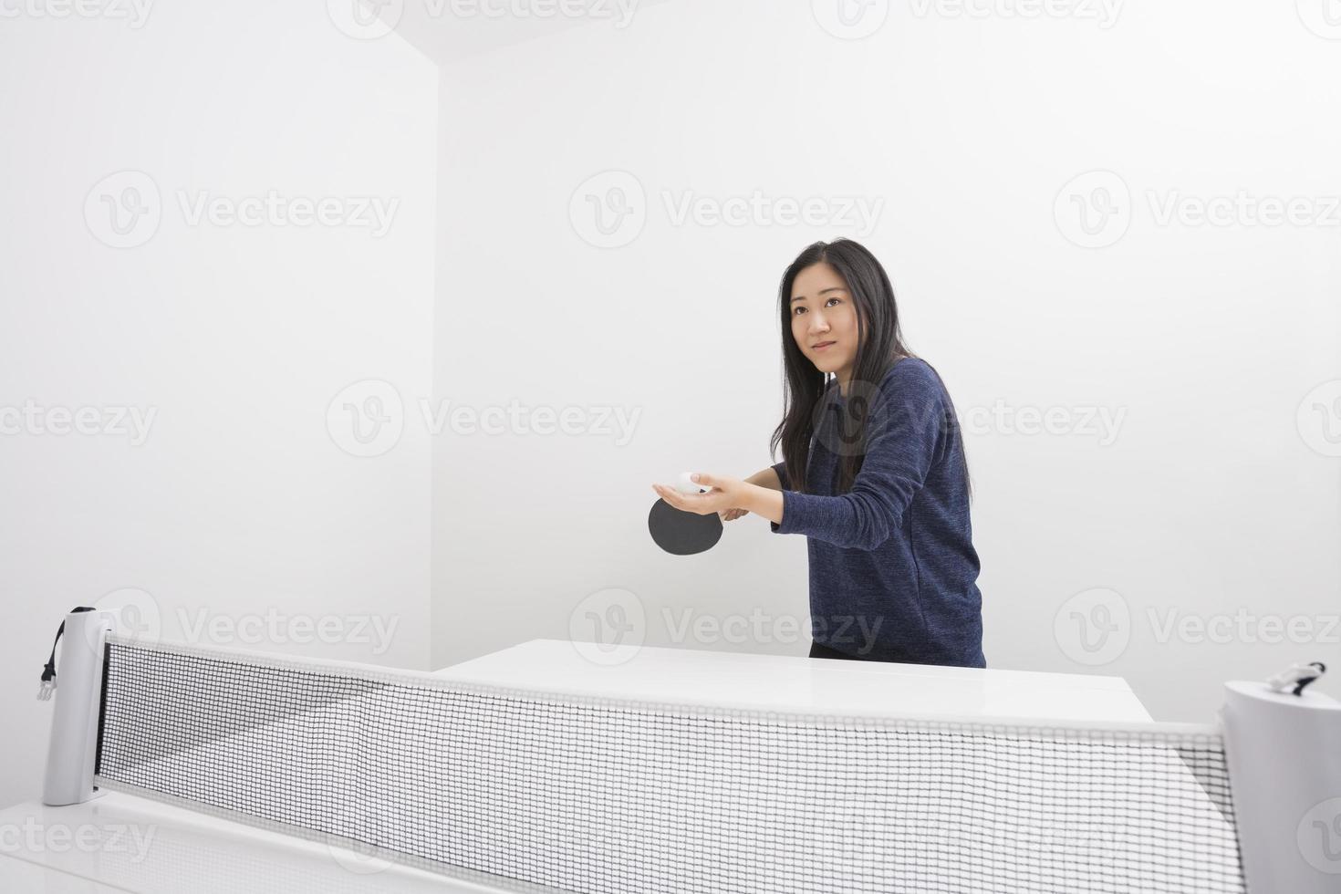 schöne junge Frau, die bereit ist, Tischtennisball zu dienen foto