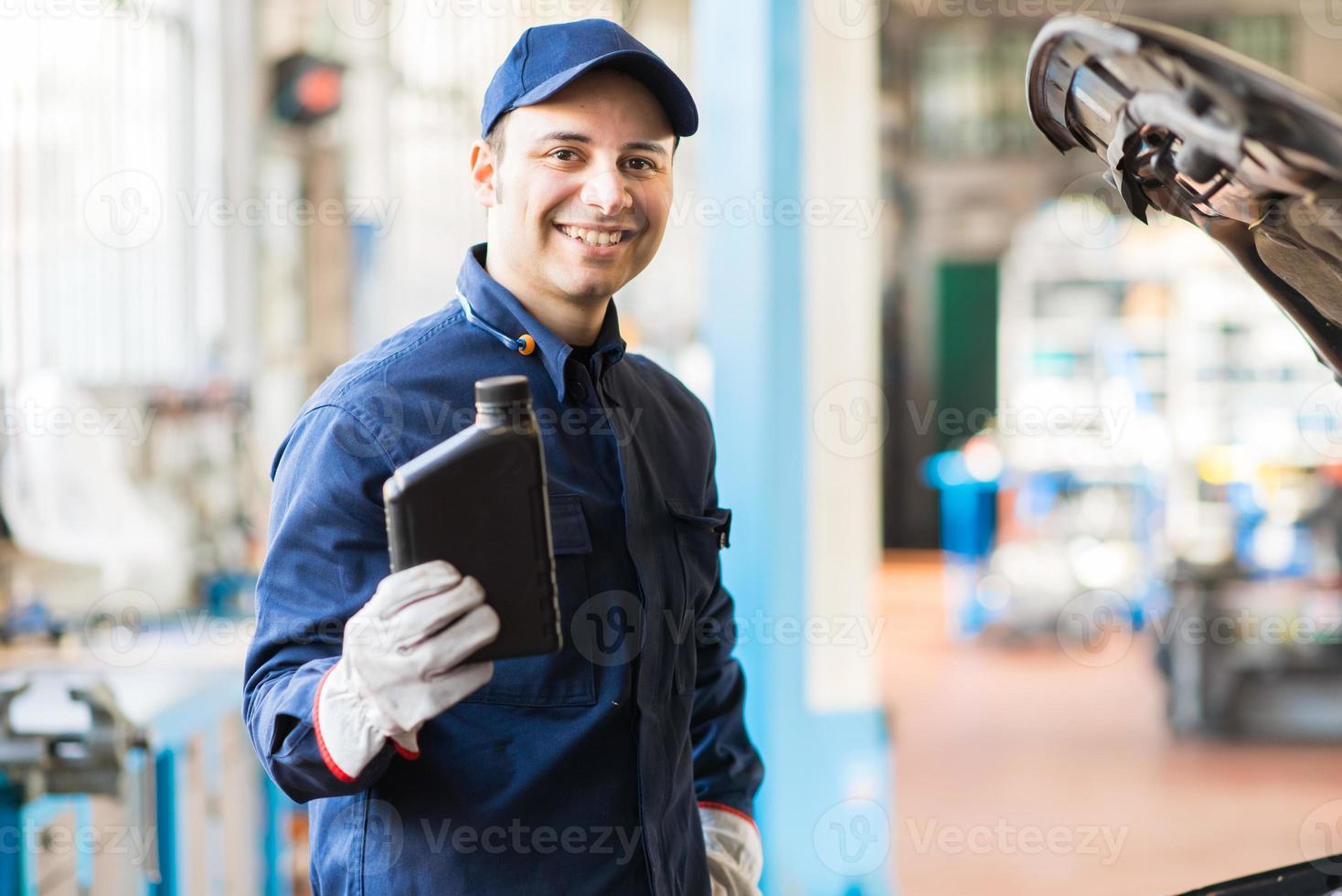 Automechaniker hält einen Krug Motoröl foto