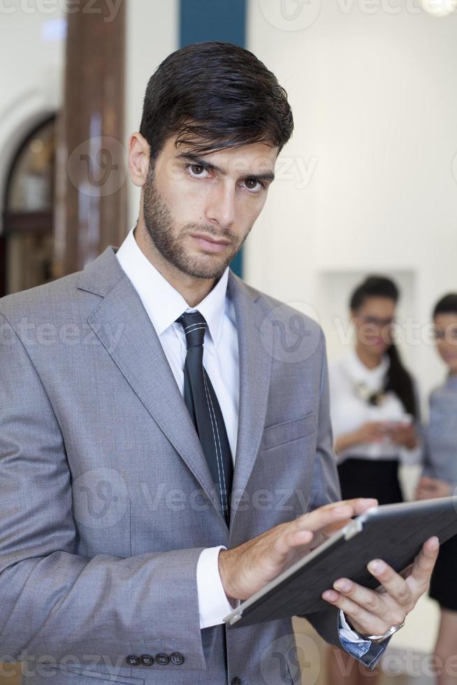 Geschäftsmann, der an der digitalen Tablette arbeitet foto