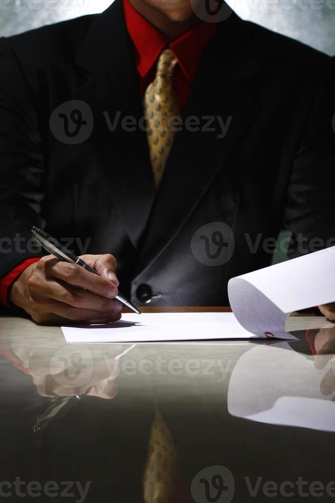 Mann, der auf ein Papier schreibt und eine Seite umblättert foto