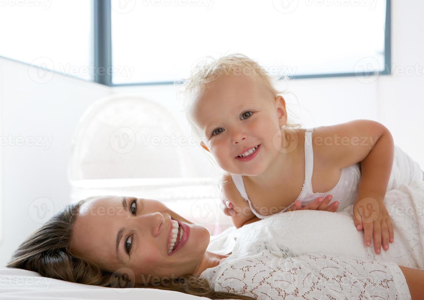 glückliche Mutter, die mit niedlichem kleinen Mädchen lächelt foto