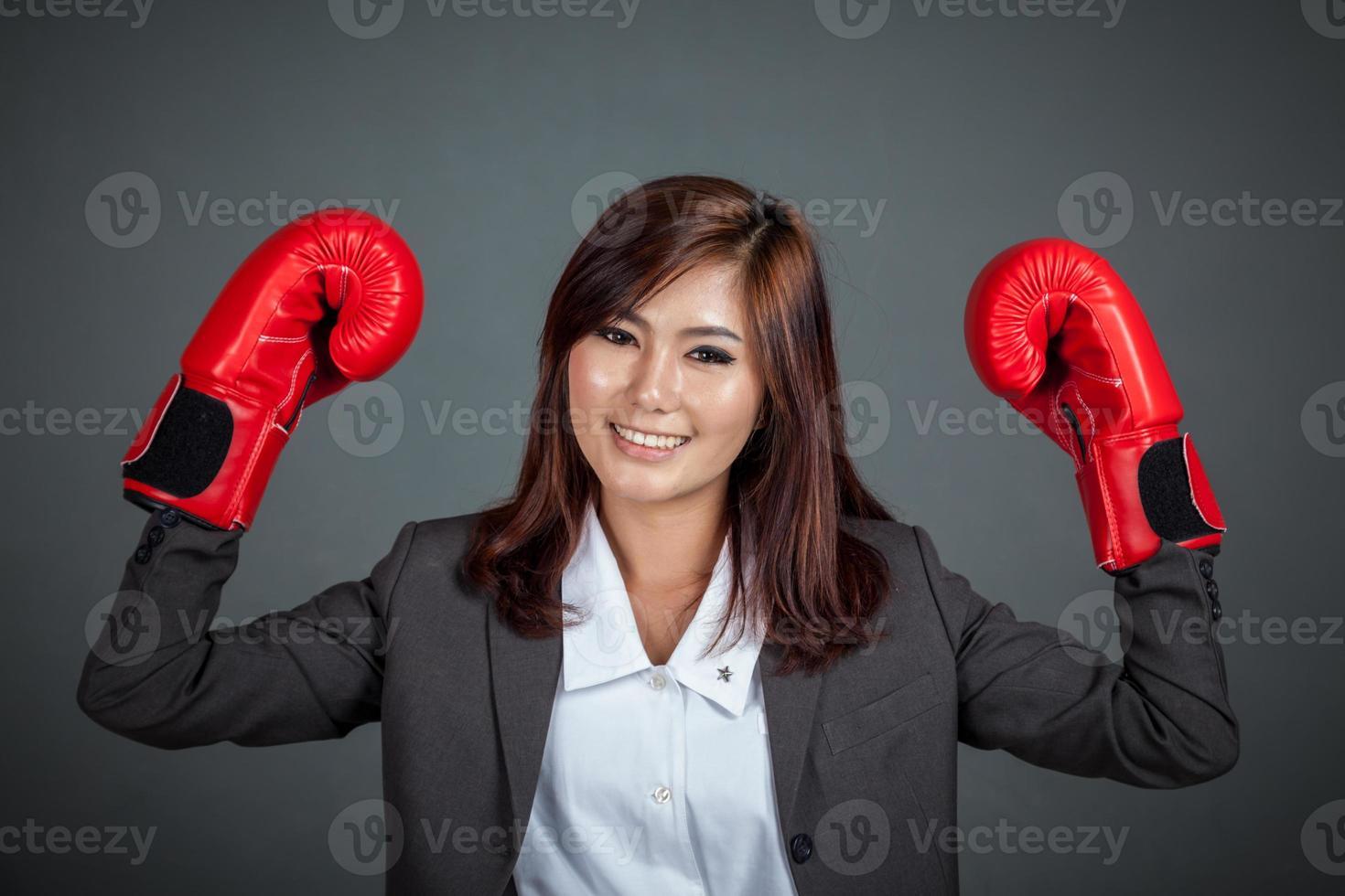 asiatische Geschäftsfrau mit Boxhandschuh zeigen ihre Fäuste foto