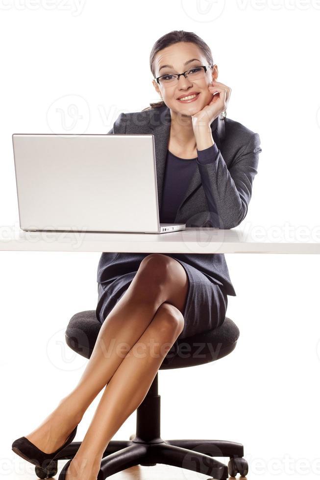 lächelnde Geschäftsfrau, die am Tisch mit Laptop sitzt foto