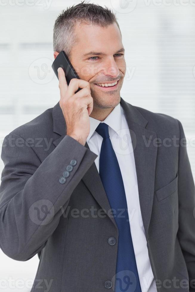 nachdenklicher Geschäftsmann, der beim Telefonieren aufwirft foto