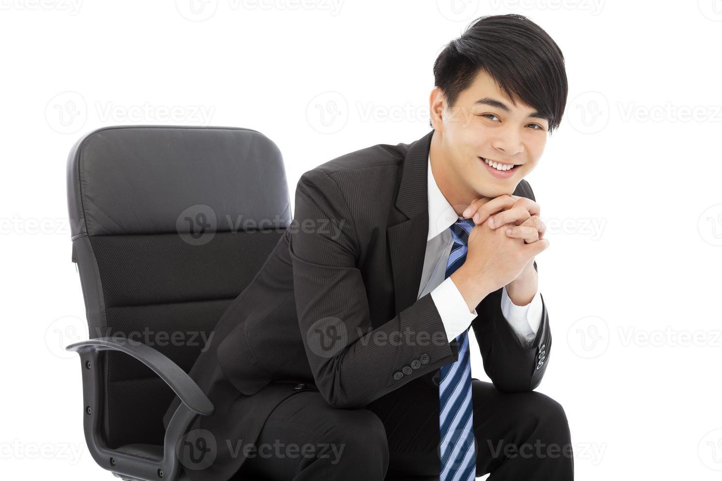lächelnder junger Geschäftsmann, der auf einem Stuhl sitzt foto
