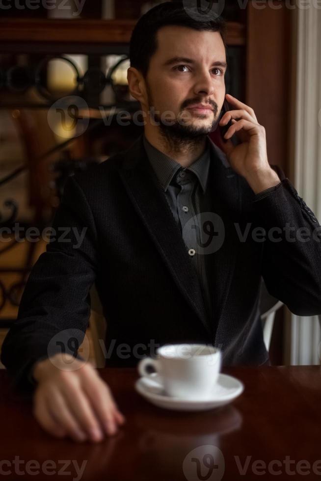 hübscher Geschäftsmann, der in einem Café am Telefon spricht foto
