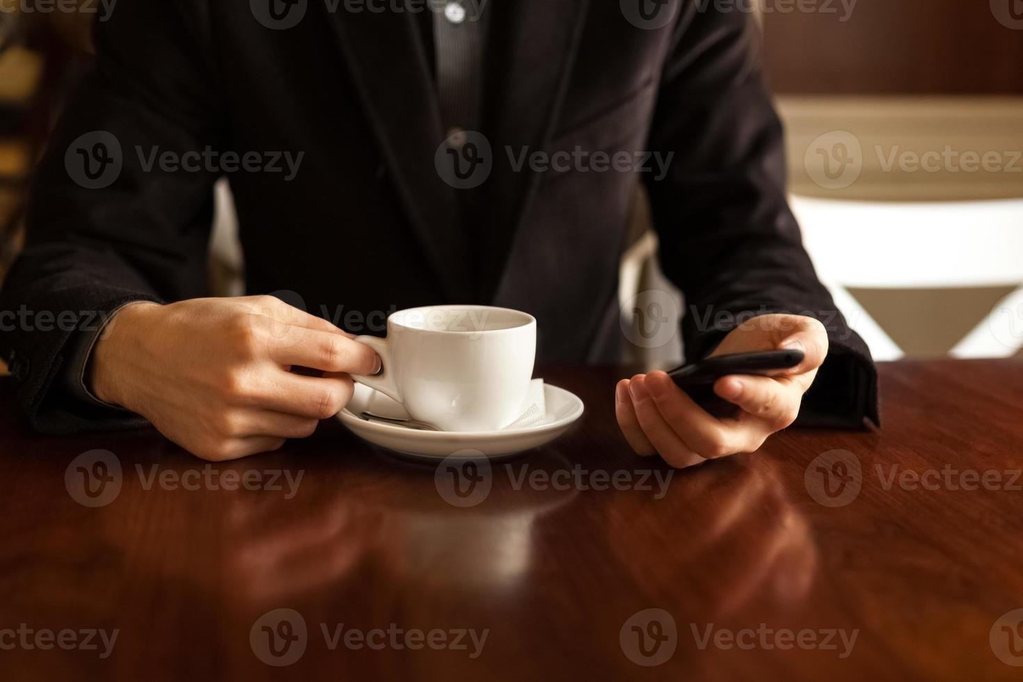 Mann, der Kaffee trinkt und ein Handy benutzt. foto