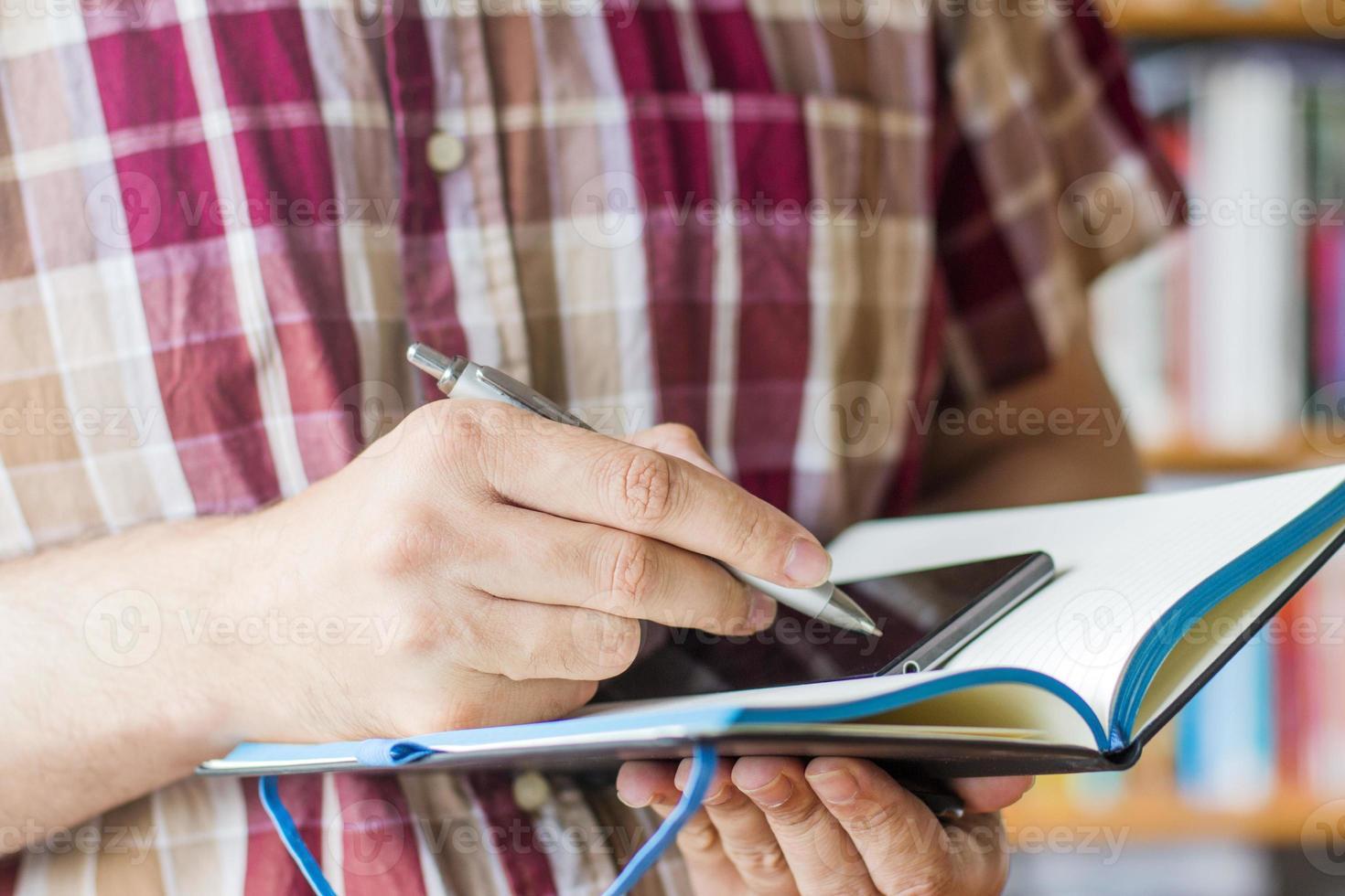 Mann schreibt in Notizbuch foto