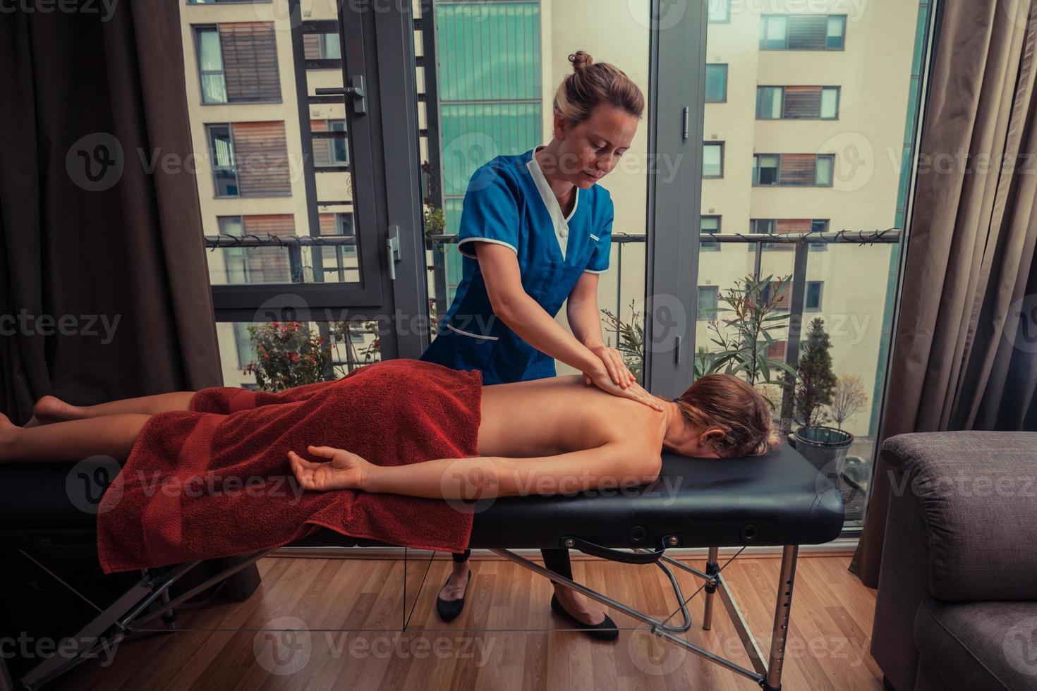 Massagetherapeut, der den Patienten zu Hause behandelt foto