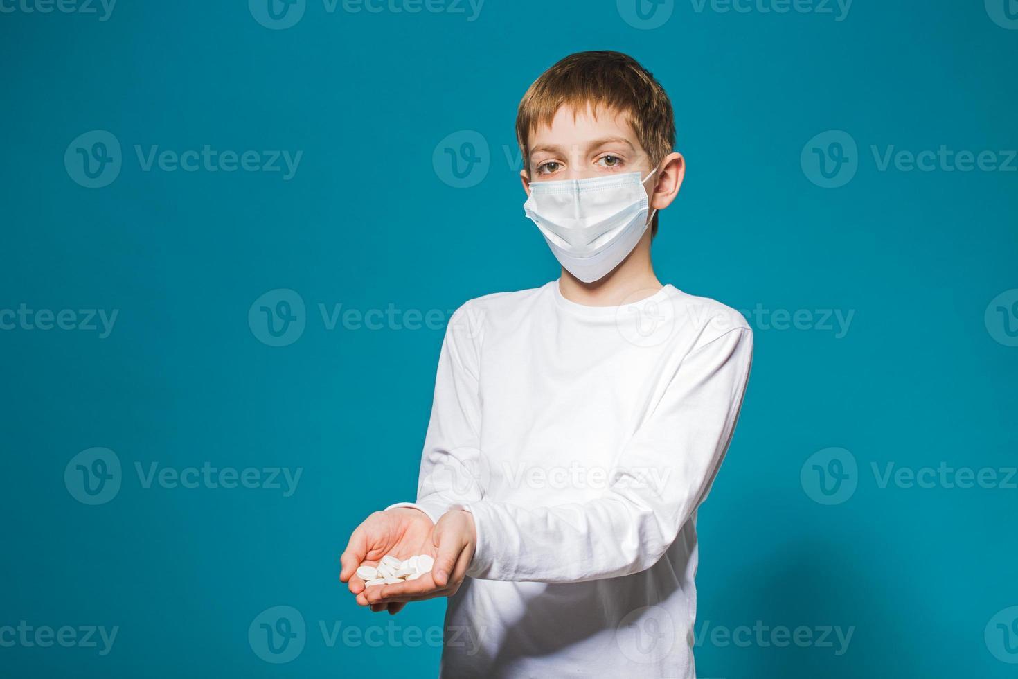 Junge in der weißen Schutzmaske, die Pillen hält foto