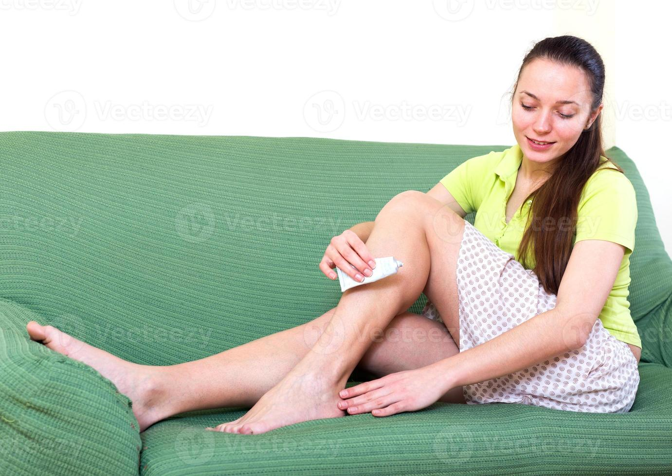 Frau, die Gel auf die Füße aufträgt foto