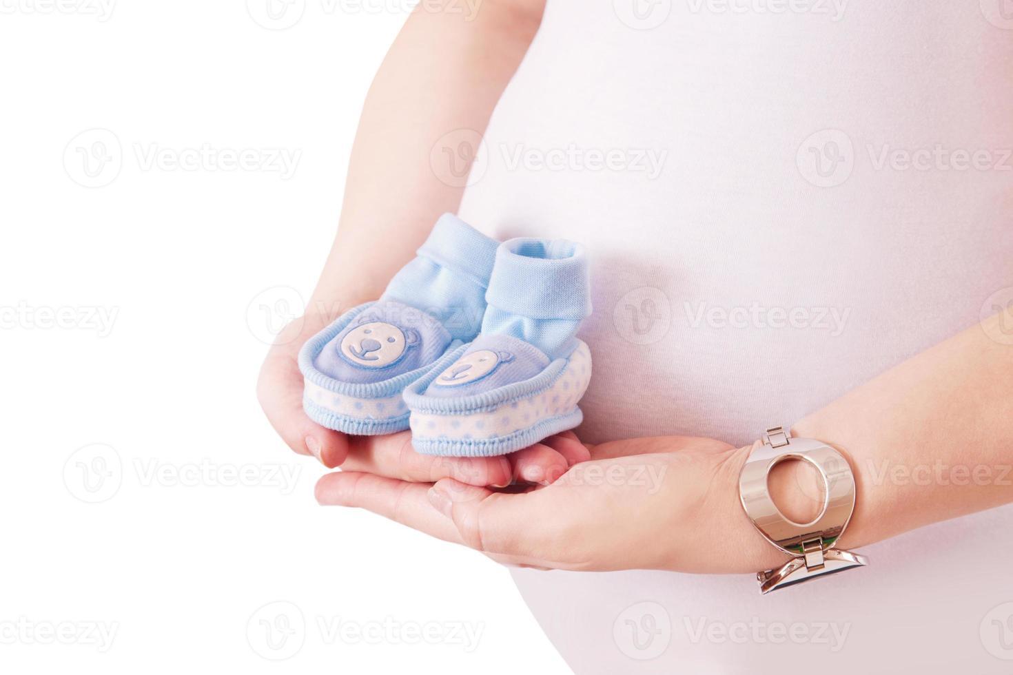 schwangere Frau, die ein Paar blaue Schuhe für Baby hält foto