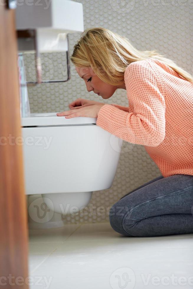 Teenager-Mädchen, das sich im Badezimmer unwohl fühlt foto