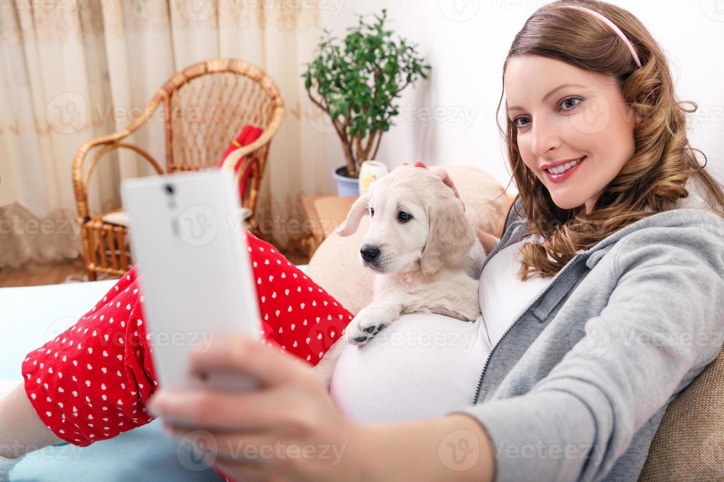 schwangere Frau mit ihrem Hund zu Hause foto