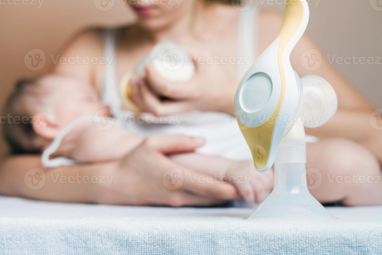 manuelle Milchpumpe und Mutter füttern ein Neugeborenes foto