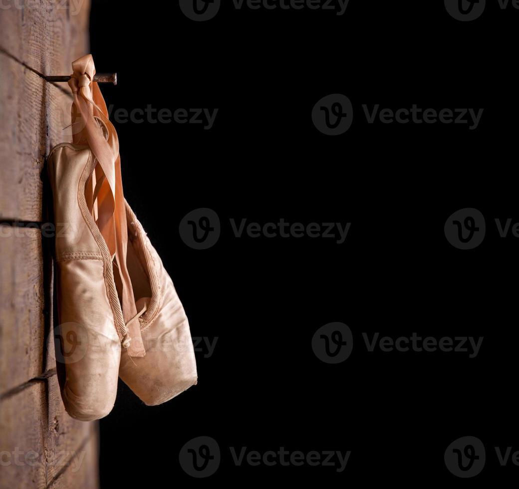 gebrauchte Ballettschuhe hängen auf hölzernem Hintergrund foto