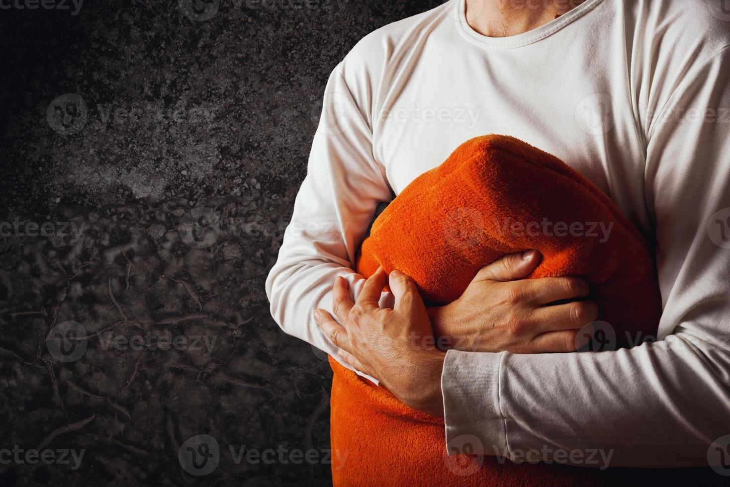Mann, der orange Kissen umarmt foto