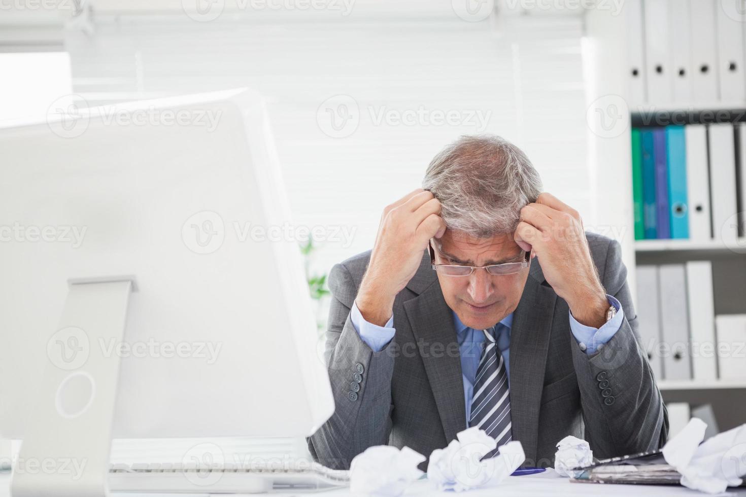 gestresster Geschäftsmann mit Kopf in Händen foto