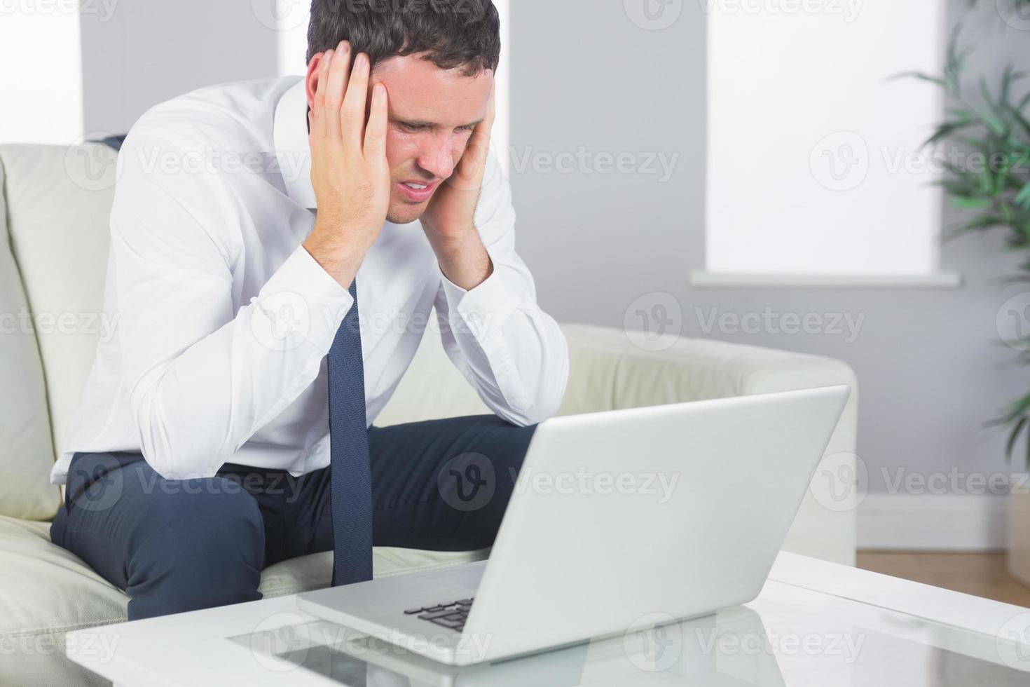 verärgerter gutaussehender Geschäftsmann, der Kopfschmerzen hat foto