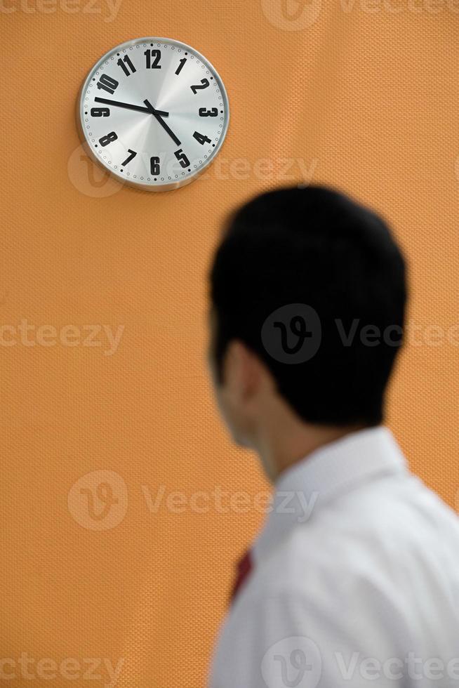 Büroangestellter, der eine Wanduhr betrachtet foto