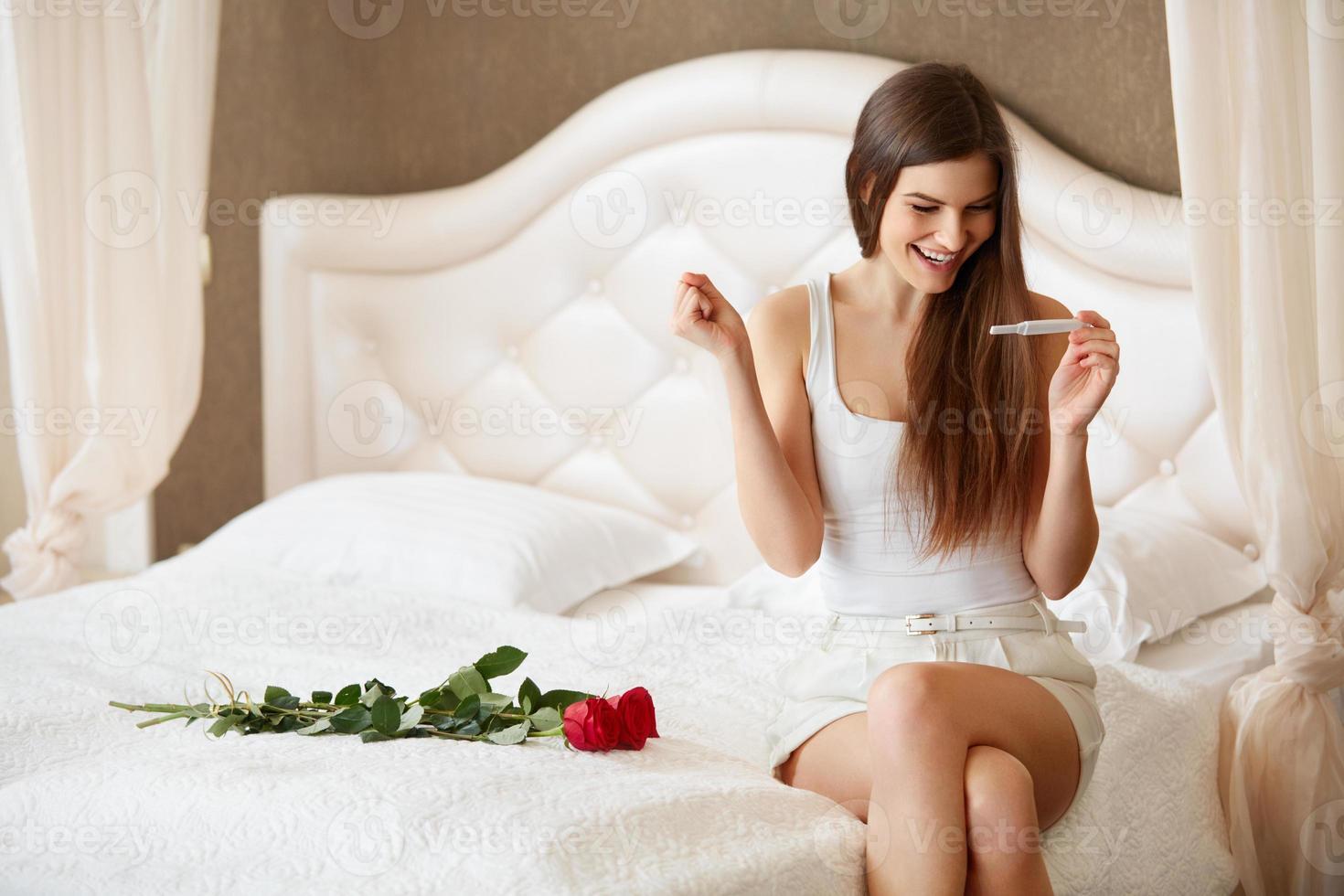 glückliche Frau mit Schwangerschaftstest foto