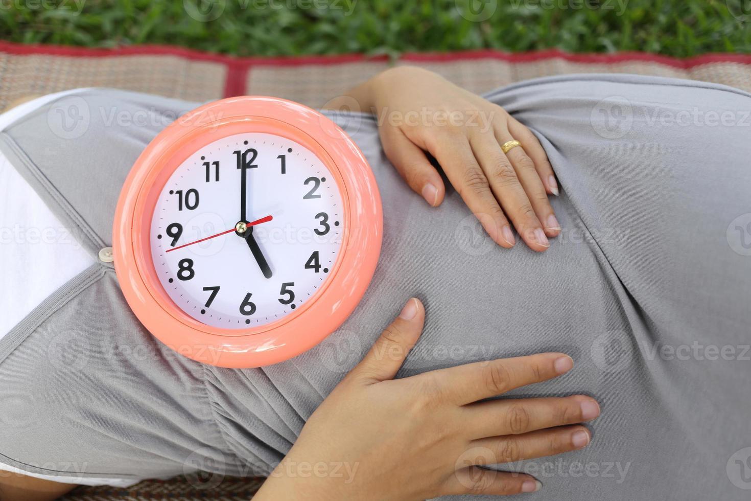 Schwangere zeigen Uhr auf ihrem Bauch. foto