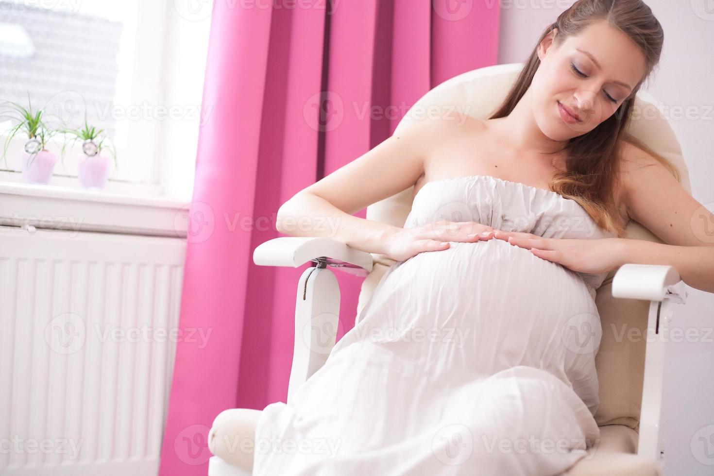 schwangere Frau auf einem Stuhl foto