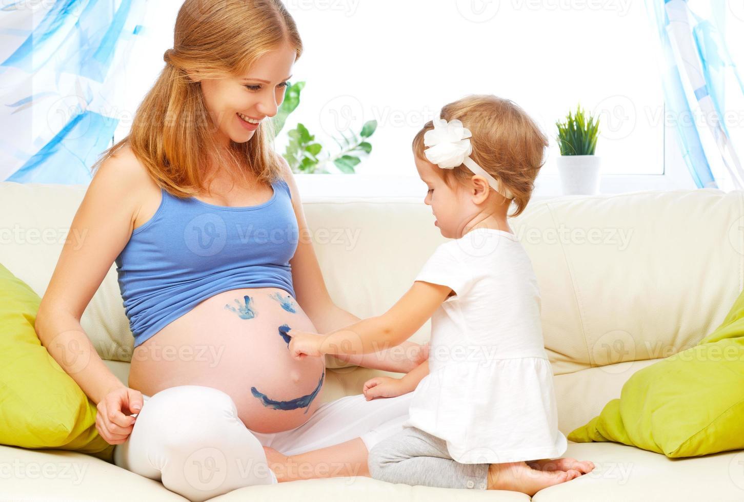glückliche Familie in Erwartung des Babys. schwangere Mutter und Kind foto