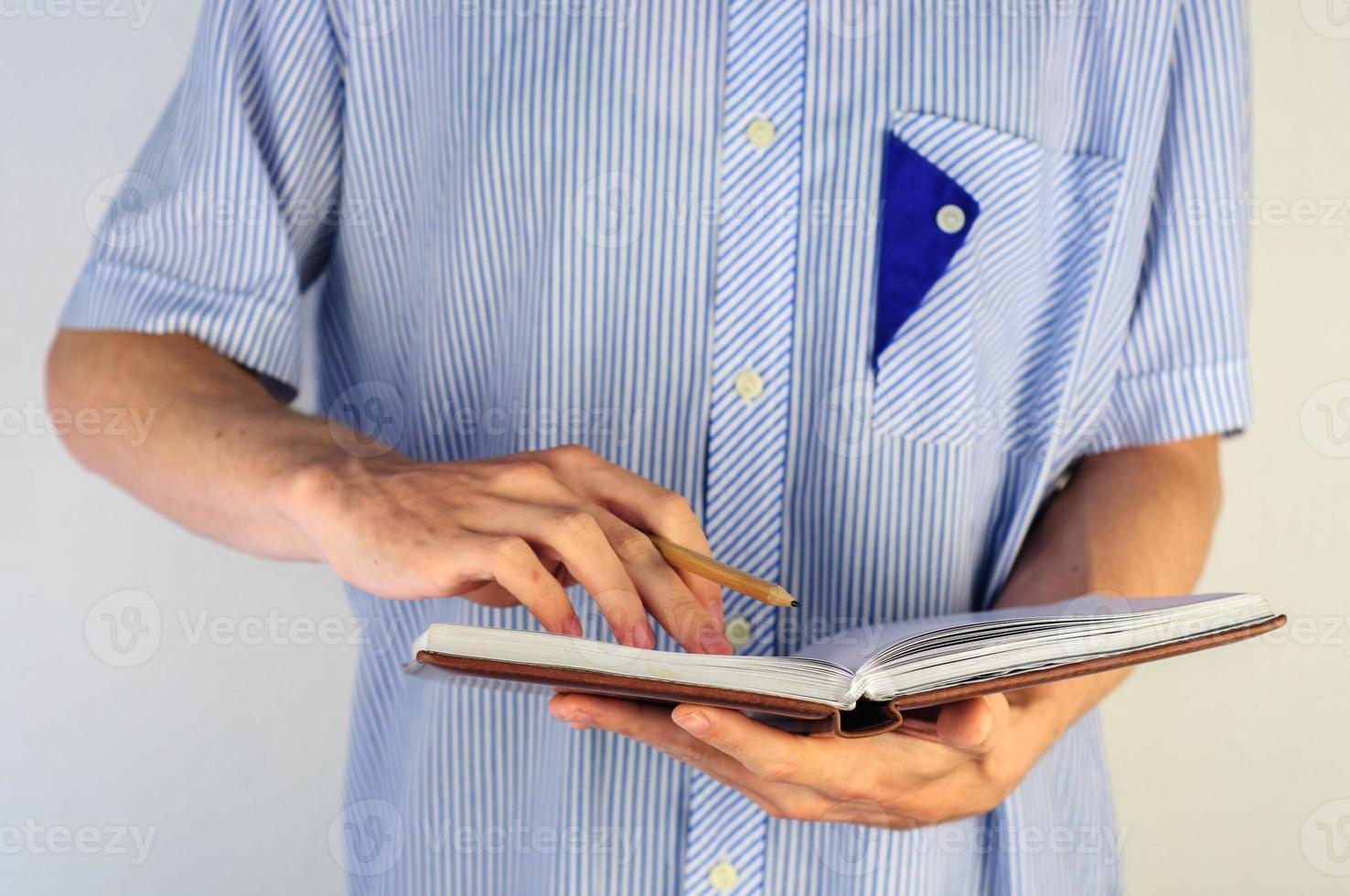 Mann im Hemd, der in sein Notizbuch schreibt foto
