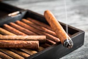 Rauch steigt von einer brennenden Zigarre auf foto